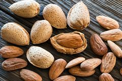 Shelled and unshelled almonds on old wood. Closeup of shelled and unshelled almonds on old wood Royalty Free Stock Photography