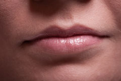Closeup shiny female lips. Part of face. Makeup and beauty. Royalty Free Stock Photos