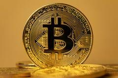 Closeup of shiny gold bitcoin on yellow backgound. Close-up of a shiny gold bitcoin in pile of coins. Virtual money or blockchain cryptocurrency stock photos