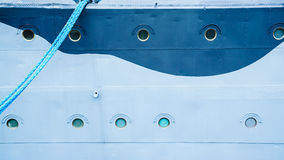 Closeup of ship with hanging mooring rope Royalty Free Stock Image