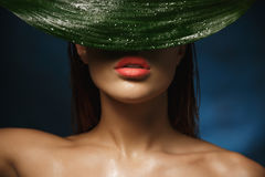 Closeup of shirtless woman with beautiful collarbone hiding behind leaf. Closeup of shirtless woman with beautiful collarbone hiding face behind big wet leaf Stock Images