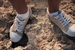 Closeup of shoes on a background of stones on the coast. Cyprus - Mediterranean Sea coast. Sea Caves near Ayia Napa. Royalty Free Stock Photography