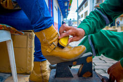 Closeup of shoeshiner working on yellow boots in Stock Photos