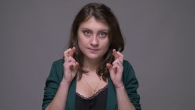 Closeup shoot of adult attractive brunette female having her fingers crossed and being anxious looking at camera with. Background isolated on gray stock video