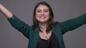 Closeup shoot of adult attractive brunette female turning around and smiling with excitement looking at camera with. Background isolated on gray stock video