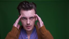 Closeup shoot of adult attractive man having a headache and being tired with background isolated on green.  stock video