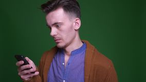 Closeup shoot of adult attractive man using the phone and looking at camera with shocked facila expression with stock video footage