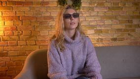 Closeup shoot of adult caucasian blonde female watching a 3D movie on the TV while sitting on the couch indoors at cozy stock video