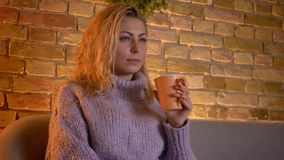 Closeup shoot of adult caucasian blonde female watching a TV comedy show holding a cup of warm tea while sitting on the stock footage