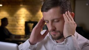 Closeup shoot of adult caucasian male employee having a headache and beind stressed and devastated indoors in the office.  royalty free stock photos
