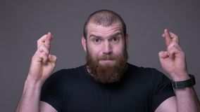 Closeup shoot of adult handsome muscular caucasian man with beard gesturing fingers crossed being anxious and hopeful. Looking at camera with background stock video footage
