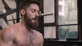 Closeup shoot of adult motivated athletic shirtless man sweating resting and using rowing machine and making resistance. Training indoors in the gym stock video footage