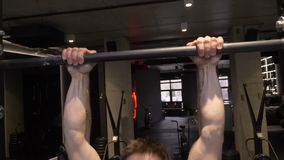 Closeup shoot of adult muscular athletic bodybuilder lifting himself on the bars indoors in the gym.  stock video