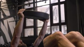 Closeup shoot of adult muscular athletic bodybuilder swingning press and lifting weights sweating indoors in the gym.  stock video footage