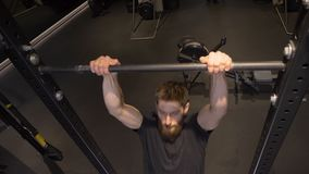 Closeup shoot of adult muscular athletic bodybuilder training and lifting himself on the bars indoors in the gym.  stock video footage