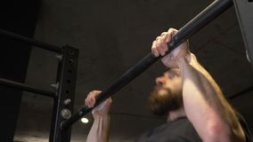Closeup shoot of adult muscular athletic man lifting himself on the bars indoors in the gym.  stock footage