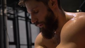 Closeup shoot of adult muscular athletic man sitting and being devastated sweating indoors in the gym.  stock video