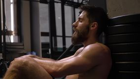 Closeup shoot of adult muscular athletic man sitting and being tired indoors in the gym.  stock footage