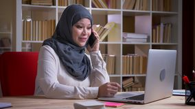 Closeup shoot of adult muslim businesswoman in hijab having a formal conversation on the phone typing on the laptop on. The workplace indoors stock video