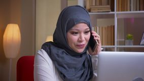 Closeup shoot of adult muslim businesswoman in hijab having a formal conversation on the phone while using the laptop on. The workplace indoors stock footage