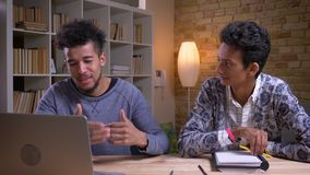 Closeup shoot of african american and indian male students having a funny discussion together. One is using on the. Laptop while another is taking notes stock footage