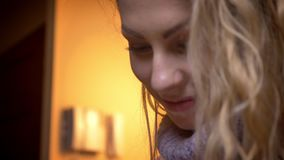 Closeup shoot by camera moving from the female hands typing on the tablet to beautiful womans smiling face in a cozy. Apartment indoors stock footage