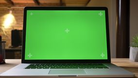 Closeup shoot by camera moxing from bottom up of the laptop with green screen on the table indoors in the office stock footage