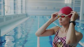 Closeup shoot of confident female swimmer putting on goggles on her face for underwater floating, She wear swimsuit and. Closeup of confident female swimmer stock footage