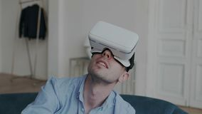 Closeup shoot of excited millennial guy using virtual reality VR headset glasses feeling wondering and surprised by stock video footage