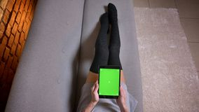 Closeup shoot of female legs in cute socks on the couch indoors. Female holding the tablet with green screen vertically.  stock image