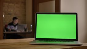 Closeup shoot of green screen of the laptop laying on the desk in office indoors with businessman working on the blurred stock video