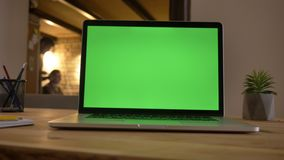 Closeup shoot of a green screen of the laptop lying on the desk in office indoors with employees interacting on the stock video footage
