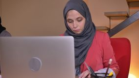 Closeup shoot of group of three young muslim female employees in hijabs working in office. One office worker drinking stock video footage