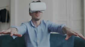 Closeup shoot of male hands moving in the space while using virtual reality glasses at home. Guy getting experience. Using VR 360 deegres headset goggles. He stock footage