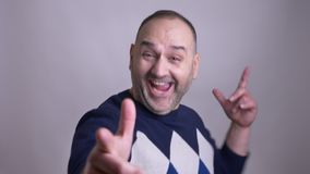 Closeup shoot of middle aged caucasian male turning to the camera smiling cheerfully and saluting with his fingers. Making a gun handsign stock video