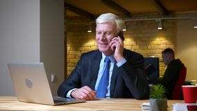 Closeup shoot of old caucasian businessman having a conversation on the phone smiling happily while using the laptop stock footage