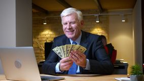 Closeup shoot of old caucasian businessman showing money smiling happily sitting in front of the laptop indoors in the