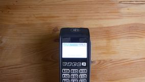Closeup shoot of a payment terminal being used for payment by an app on the phone indoors. Hand being scanned by. Electronics stock photo