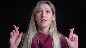Closeup shoot of pretty caucasian blonde female having her fingers crossed with hope and anxiety.  stock footage