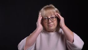 Closeup shoot of senior caucasian blonde female in glasses having a headache and being tired with background isolated on. Black stock footage