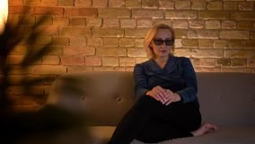 Closeup shoot of senior caucasioan female watching a 3D action movie on TV in glasses indoors.  stock footage