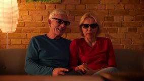 Closeup shoot of senior happy couple watching a 3D movie on TV resting sitting on the couch indoors in a cozy apartment stock video footage