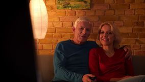 Closeup shoot of senior happy couple watching a TV show smiling with excitement sitting on the couch indoors in a cozy. Apartment stock video footage