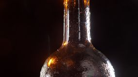 Closeup shoot of shiny wet cold beer bottle neck in motion spinning around.  stock video footage