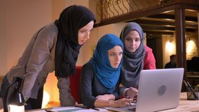 Closeup shoot of three outgoing muslim female employees having a discussion using the laptop then looking at camera and. Smiling stock footage