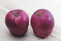 Closeup shoot of two red apples. Red apples on wooden background Stock Photos