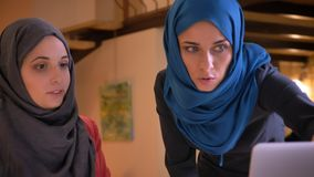 Closeup shoot of two young arabian female office workers in the hijabs discussing the data on the graph.  stock video