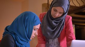 Closeup shoot of two young arabian female office workers in the hijabs discussing the data on the graph. Younger. Employee asks workmate for an advice stock footage