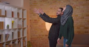 Closeup shoot of young attractive arabian couple settling in a newly bought apartment indoors.  stock footage