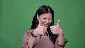 Closeup shoot of young attractive asian female with black hair smiling and gesturing thumb up showing agreement with. Background isolated on green stock video
